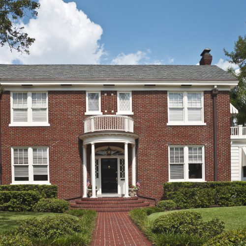 Federal style colonial home. The entrance to a traditional American home. Includes brick exterior walls, portico,  porte-cochere, Palladian window above the front door, porch, balcony, and expansive front yard. Space for copy.