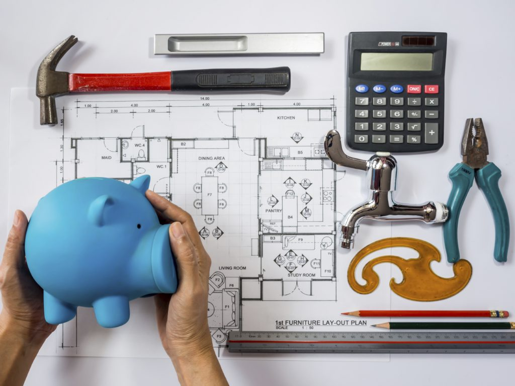 Hands holding piggy bank over architecture drawing, planning for home remodel / saving concept