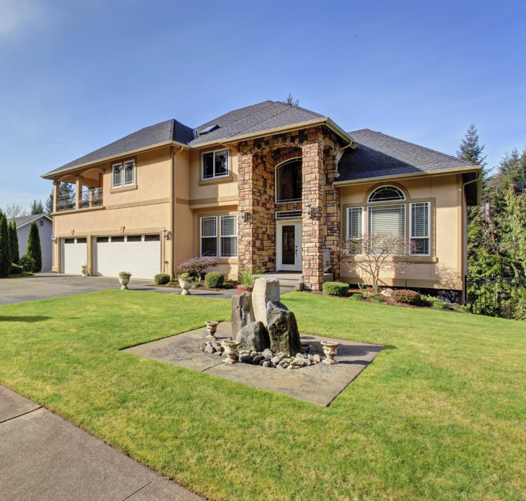 Luxury home wth large grass yard and garage.